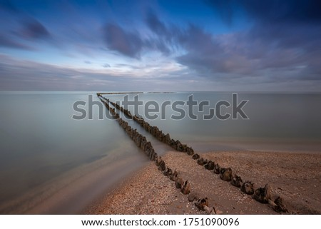 Holland - An old, dilapidated, wooden breakwater, begins on the edge of a sandy beach and ends in the sea. For a long time calmed the sea, dynamic sky. Romantic atmosphere.  #1751090096