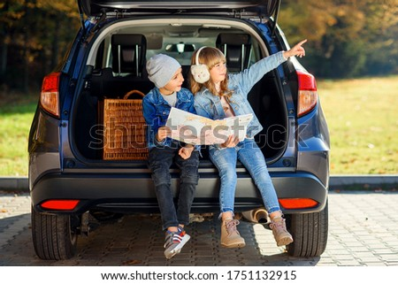Cute stylish brother and pretty sister studying the road map in detail while sitting in the auto's trunk and discussing right direction. Family vacation trip by car. Royalty-Free Stock Photo #1751132915