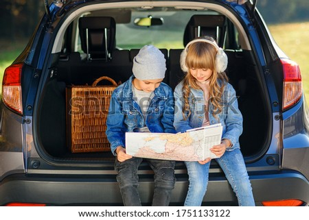 Cute stylish boy and pretty 10-s girl looking at the road map while sitting in the auto's trunk and discussing right direction to their family trip. Family vacation trip by car. Royalty-Free Stock Photo #1751133122
