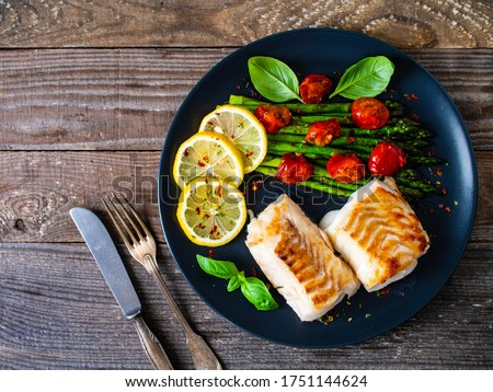 Fish dish - fried cod fillet with asparagus and cherry tomatoes served on black plate on wooden table