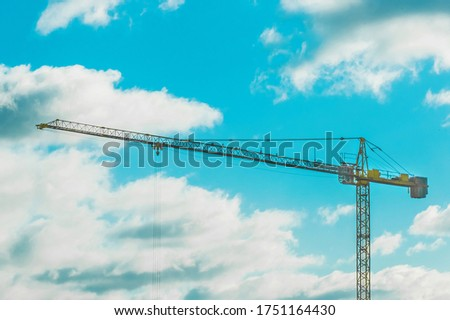 Tower crane on a background of blue sky with white clouds #1751164430
