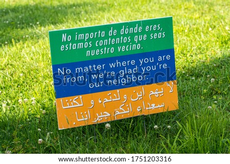 This sign on a lawn welcomes people to the neighborhood in 3 languages, spanish, english and arabic and is creative commons so many people will print it and welcome all to their community.
