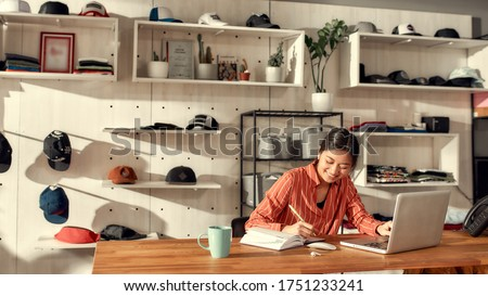Portrait of young female worker making notes, receiving online orders while sitting in the office. Woman working at custom T-shirt, clothing printing company. Horizontal shot. Selective focus