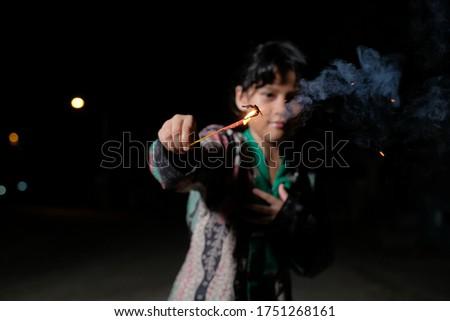 Malay girl celebrating Hari Raya Aidilfitri playing firework in hand