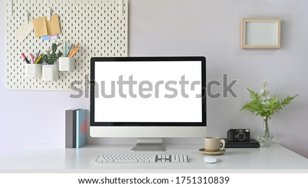 Computer monitor with white blank screen putting on white working desk that surrounded by retro camera, plant in glass vase. coffee cup, wireless mouse, keyboard, book and document file.