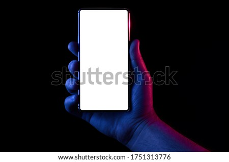Phone in hand. Silhouette of male hand lit with blue and red neon lights holding bezel-less smartphone on black background. Screen is cut with clipping path. Royalty-Free Stock Photo #1751313776
