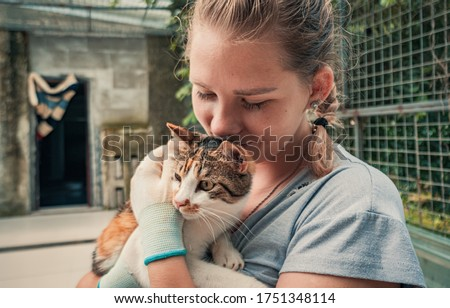 Close-up of female volunteer holds on hands cat in shelter. Shelter for animals concept Royalty-Free Stock Photo #1751348114