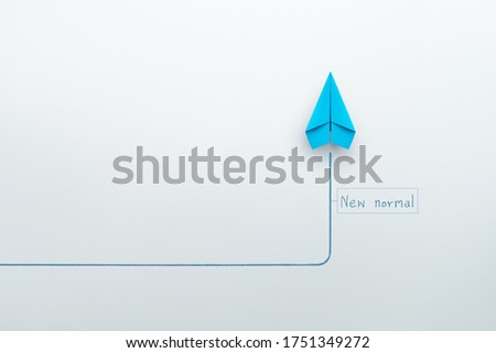 New normal concept with blue paper plane in new direction on white background, copy space