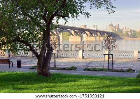 The embankment of the river Ob. The view from the Park at St. Michael the embankment on the bridge and tall buildings on the horizon. A bench, a paved path without people, a lattice fence  Royalty-Free Stock Photo #1751350121