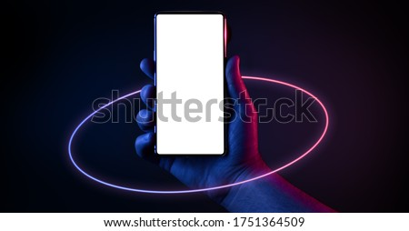 Phone in hand. Silhouette of male hand holding bezel-less smartphone with futuristic neon light circle on dark background. Screen is cut with clipping path. #1751364509