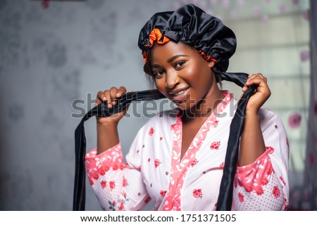 Elegant black lady looking at camera wearing a satin bonnet and floral robe, smiling in interior. Black female health and wellness indoors, skin perfection and care lifestyle. Royalty-Free Stock Photo #1751371505