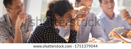 Laughing indian businesswoman in friends company eating pizza enjoy lunch together with colleagues, team building corporate party, friendship concept. Horizontal photo banner for website header design