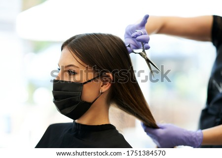 Adult woman at hairdresser wearing protective mask due to coronavirus pandemic Royalty-Free Stock Photo #1751384570