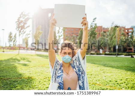 Young mixed race woman holding blank banner outdoors - woman protesting holding customable sign