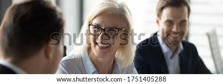 Mature businesswoman lead negotiations, during business meeting with company investor or client businesspeople laughing enjoy friendly talk concept. Horizontal photo banner for website header design