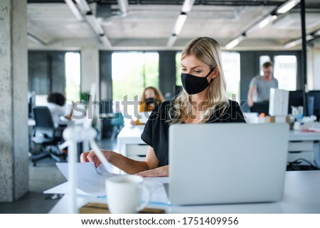 Young woman with face mask back at work in office after lockdown, working. Royalty-Free Stock Photo #1751409956