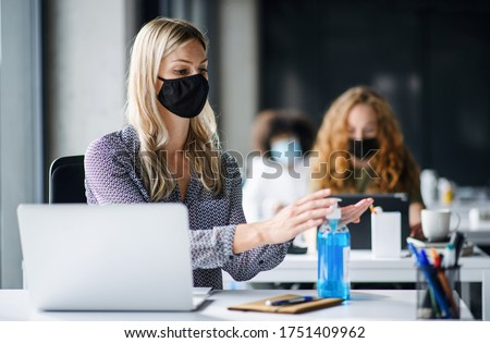 Young woman with face mask back at work in office after lockdown, disinfecting hands. #1751409962
