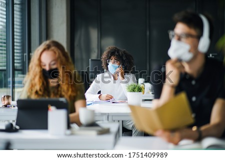 Young people with face masks back at work or school in office after lockdown. Royalty-Free Stock Photo #1751409989