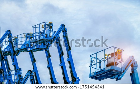 Articulated boom lift. Aerial platform lift. Telescopic boom lift against blue sky. Mobile construction crane for rent and sale. Maintenance and repair hydraulic boom lift service. Crane dealership.  #1751454341
