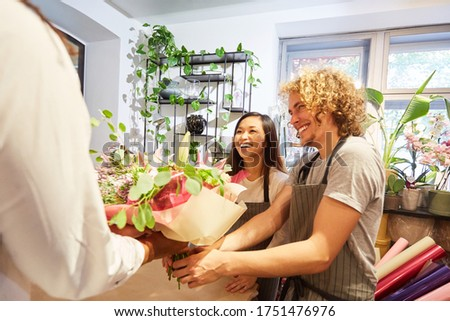 Start-up florist team is happy about opening bouquet of flowers #1751476976