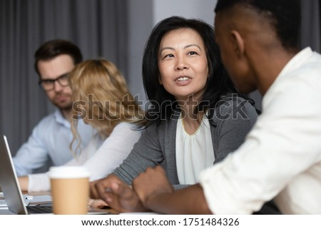 Focus to asian ethnicity middle-aged woman mentor more experienced worker teach African guy millennial intern, diverse staff members sitting in co-working shared room working on common project concept #1751484326