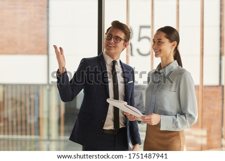 Waist up portrait of smiling real estate agent discussing property with female client and pointing up while standing in empty office building interior lit by sunlight, copy space Royalty-Free Stock Photo #1751487941