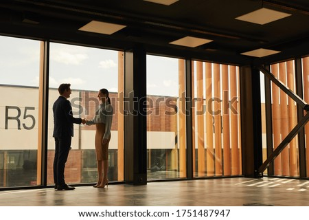Wide angle view of real estate agent shaking hands with client while standing in empty office building interior lit by sunlight, copy space Royalty-Free Stock Photo #1751487947