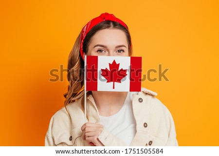 A young woman covers her face with a small flag of Canada, Canada Day celebration. Student girl holding the flag of Canada, education abroad #1751505584