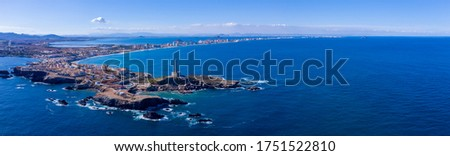 Panorama shot hovering over the southern end of the Cabo de Palos Lighthouse, in the background is La Manga del Mar Menor