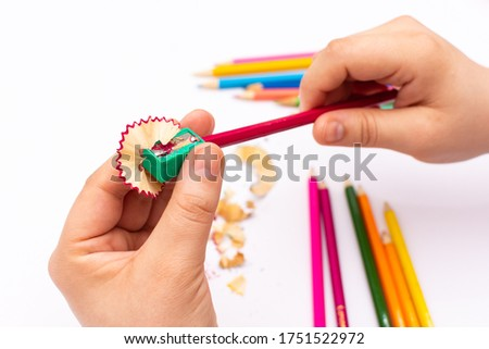 unrecognizable person sharpening a colored pencil on a white background
