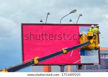 Two workers install red billboard on roadside of city street