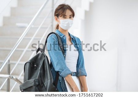 Young student woman wearing face mask to prevent infection corona virus she jean jacket and carry backpack and laptop indoor university #1751617202