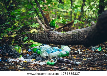 Garbage pile in forest among plants. Toxic plastic into nature everywhere. Rubbish heap in park among vegetation. Contaminated soil. Environmental pollution. Ecological issue. Throw trash anywhere. Royalty-Free Stock Photo #1751635337