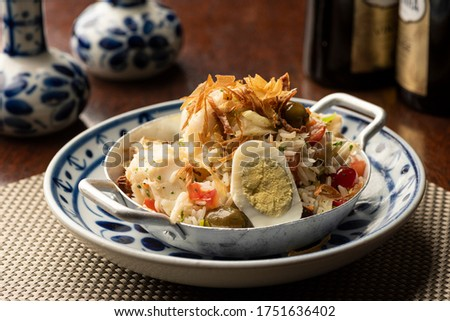 cod fish bacalhau with rice, onions eggs olive oil portuguese traditional food on wooden table mat and blurred background