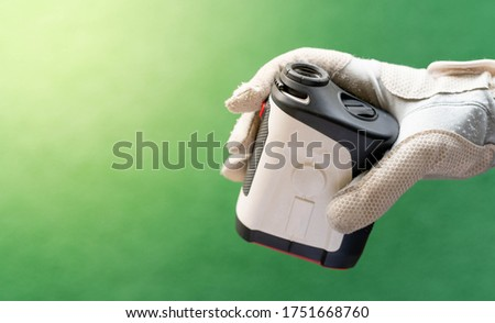 Female hands wearing professional glove with white and black modern optical range finder used for golfing or hunting. #1751668760