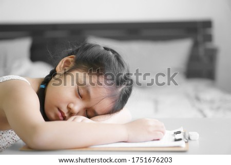 asian child student or kid girl writing or draw and doing homework or read learn and training write on paper but fall asleep or sleep rest on table by stay home safe and school study online in bedroom