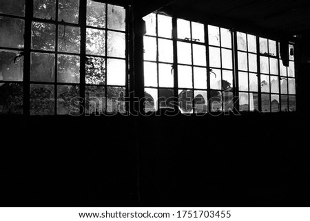 Light shining in through smashed and shattered Glass Window of derelict Factory in the Countryside Royalty-Free Stock Photo #1751703455