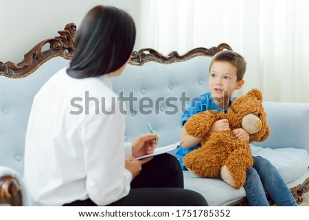 Picture of child psychologist working with young boy in office