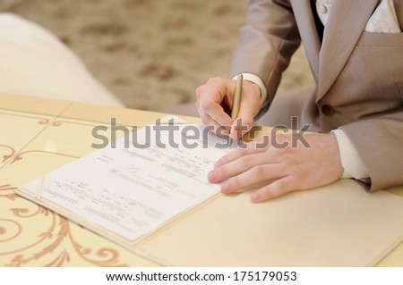 Groom signing marriage license #175179053