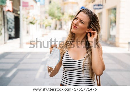 Woman taking off mask with ear gesture annoyed by mask in coronavirus pandemic Royalty-Free Stock Photo #1751791475