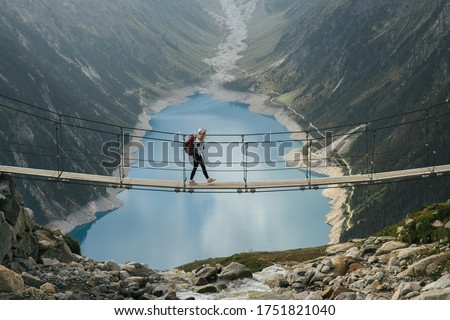 Girl traveler with a backpack in the mountains. A young girl stands on a suspension bridge on a background of mountains and glaciers. Travel and active life concept. Adventure trip to Europe. Royalty-Free Stock Photo #1751821040