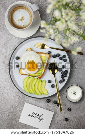 Sliced avocado and egg on toasted bread with blueberry on white plate and hot Late for breakfast. Good morning. Vertical image.