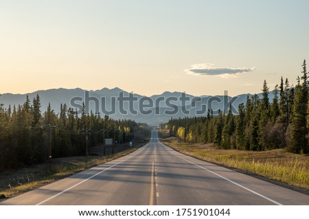 Long straight road heading towards large mountains in Yukon Territory, northern Canada in the spring time on the Alaska Highway.  Royalty-Free Stock Photo #1751901044