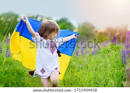 Child carries fluttering flag of Ukraine in field. Ukraine's Independence Day. Flag Day. Constitution day. Girl in traditional embroidery with flag of Ukraine #1751904458