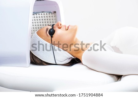 Led phototherapy for the face. Phototherapy in cosmetology. A beautiful young woman in a suit and glasses lies in the cosmetologist's office on the face phototherapy procedure. #1751904884