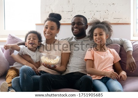 Full African ethnicity family, spouses with daughter and son spend weekend free time together at home sitting on couch in living room eating popcorn watching TV show movie or cartoons have fun concept