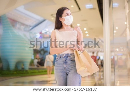 portrait of beautiful woman is wearing face mask in shopping center  #1751916137