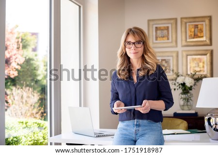 Portrait shot of middle aged woman holding digital tablet in her hand while looking at camera and smiling. Smiling businesswoman working from home. Home office. Royalty-Free Stock Photo #1751918987