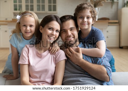 Portrait of happy young Caucasian family sit on couch in kitchen posing with little preschooler kids, smiling mother and father hug embrace small daughter and son relaxing together on weekend at home