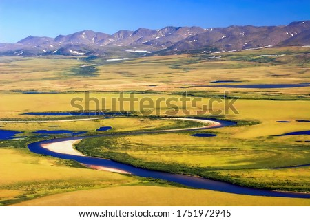 Aerial view of summer arctic landscape. Top view of the tundra, winding river and mountains. Location: Volchya River, Anadyr Tundra. Golden Ridge in the distance. Chukotka, Siberia, Far East Russia.